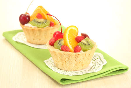 sweet cake with fruits on wooden table photo