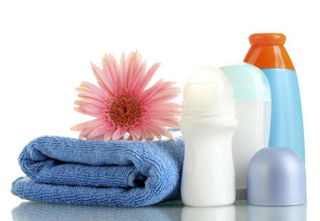 cosmetics bottles with towel and flower isolated on white photo