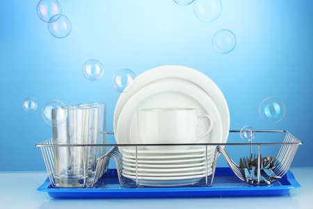 clean dishes on stand on blue background Stock Photo