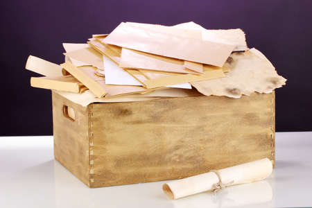 Wooden crate with papers and letters on purple background Stock Photo - 14763925