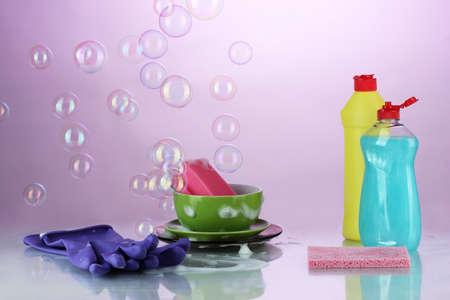 cleaning products: Lavar los platos. Los productos de limpieza en el fondo violeta brillante Foto de archivo