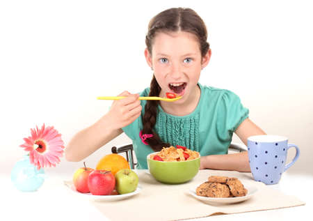little beautiful girl have a breakfast on white background photo
