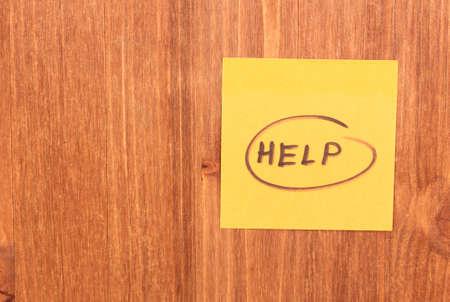 Help written on sticker on wooden background photo