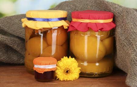 frutta sciroppata: Vasi con conserve di frutta su sfondo di legno Archivio Fotografico