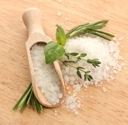 salt in shovel with fresh basil, rosemary and thyme on wooden background photo