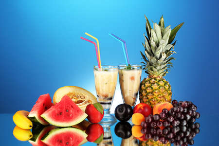 Milk shakes with fruit on blue background close-up photo
