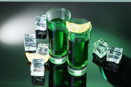 Deux verres d'absinthe, de citron et de glace sur fond vert Banque d'images - 14775668
