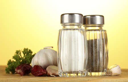Salt and pepper mills, garlic and parsley on wooden table on yellow background photo