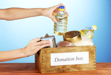 donations: Donation box with food on blue background close-up
