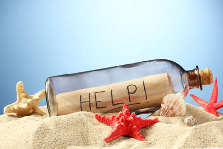 Glass bottle with note inside on sand, on blue background Stock Photo - 14807820
