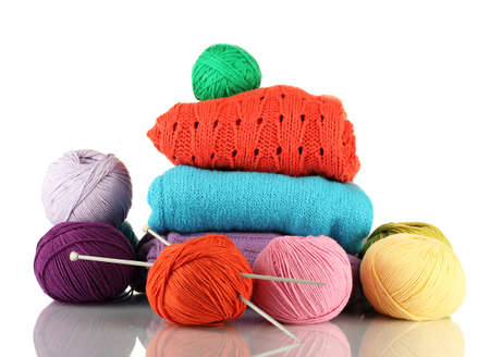 Sweaters and balls of wool isolated on white photo
