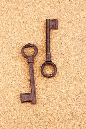 Two antique keys on cork background Stock Photo - 14822873