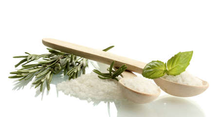 salt in spoons with fresh basil and rosemary isolated on white photo