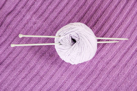 Purple sweater and a ball of wool close-up photo