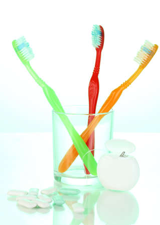 Toothbrush in glass, dental floss and chewing gum on green background photo