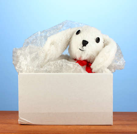 Opened parcel with a childs toy on blue background close-up photo