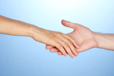 ayudando: Mano de mujer va a la mano del hombre sobre fondo azul