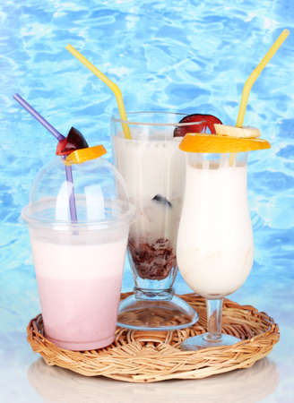 Delicious milk shakes with fruit on wicker cradle on blue sea background photo