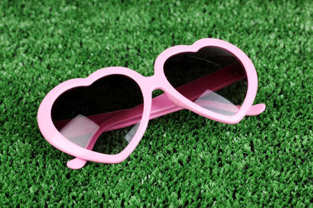 Pink heart-shaped sunglasses on green grass photo