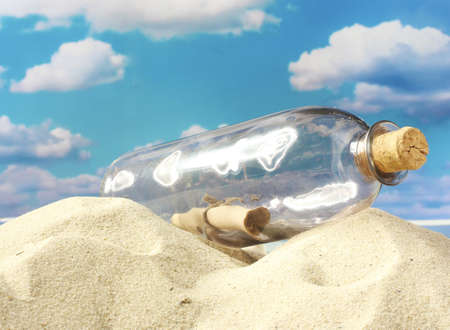 Glass bottle with note inside on sand, on blue sky background Stock Photo - 15196893
