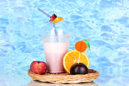 Delicious milk shake with fruit on wicker cradle on blue sea background photo