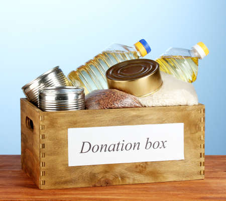 canned food: Donation box with food on blue background close-up