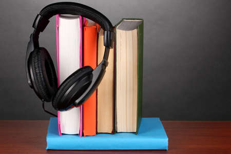 Headphones on books on wooden table on black background photo