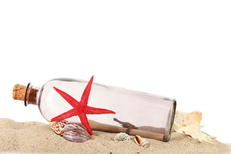 Glass bottle with note inside on sand isolated on white photo