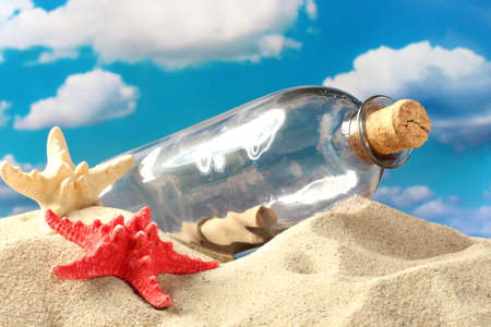 castaway: Glass bottle with note inside on sand, on blue sky background Stock Photo