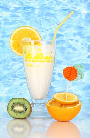 Delicious milk shakes with fruit on blue sea background photo