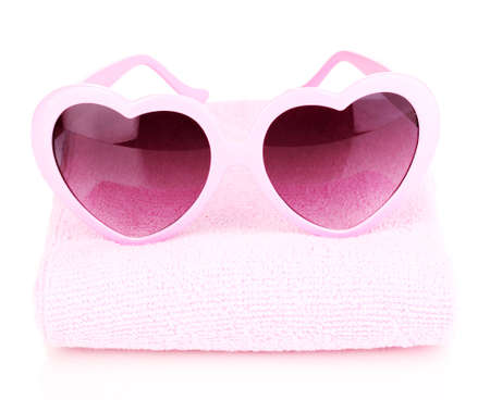 Pink heart-shaped sunglasses on towel isolated on white photo