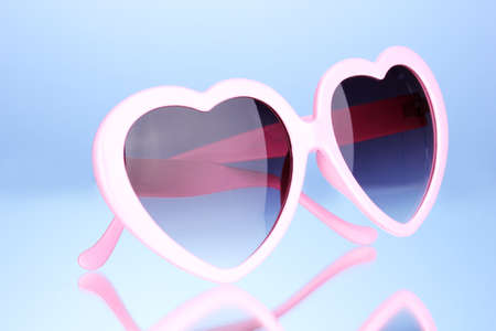 Pink heart-shaped sunglasses on blue background photo