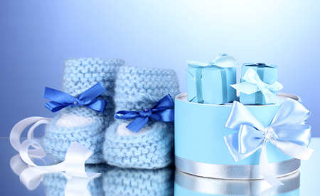 beautiful gifts and babys bootees on blue background photo
