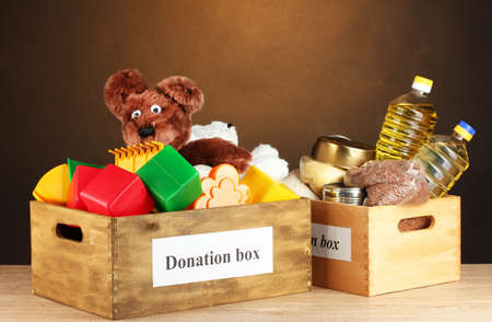 childrens food: Donation box with food and childrens toys on brown background close-up