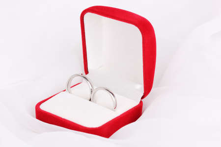 Wedding rings in red box on white cloth background