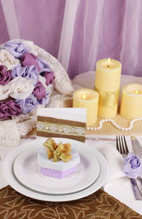 Serving fabulous wedding table in purple and gold color on\ white and purple fabric background