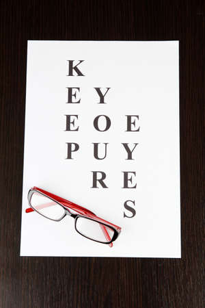 Eyesight test chart with glasses on wooden background close-up photo
