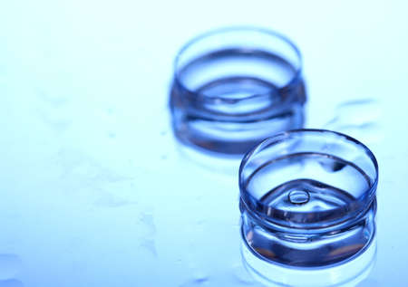 shortsightedness: contact lens with drops on blue background