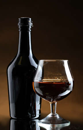 distilled alcohol: Glass of brandy and bottle on brown background