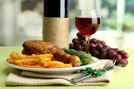 Roast chicken with french fries and cucumbers, glass of wine on green table cloth in cafe interior photo