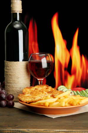 Roast chicken cutlet with french fries, glass of wine on fire background photo