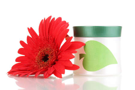 by hand: Jar of cream with flower isolated on white