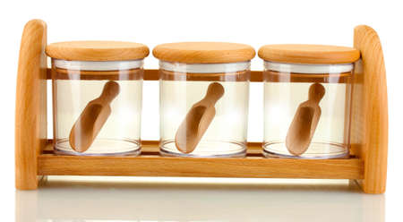 empty glass jars for spices with spoons on wooden shelf isolated on white photo