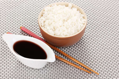 Bowl of rice and chopsticks on grey mat photo