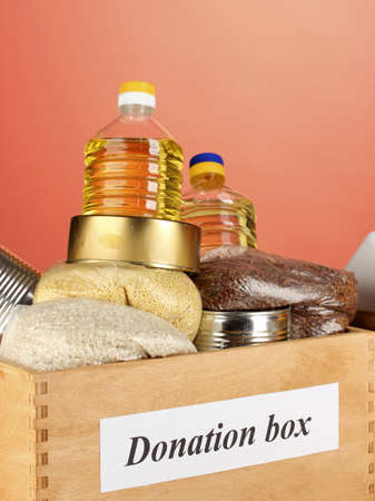 Donation box with food on red background close-up Stock Photo - 14906762