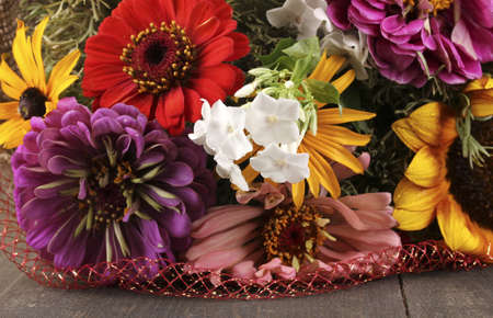 Beautiful bouquet of bright flowers in sacking on wooden background photo