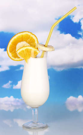 Delicious milk shake with fruit on table on sky background photo