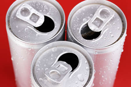 aluminum cans with water drops on red background photo