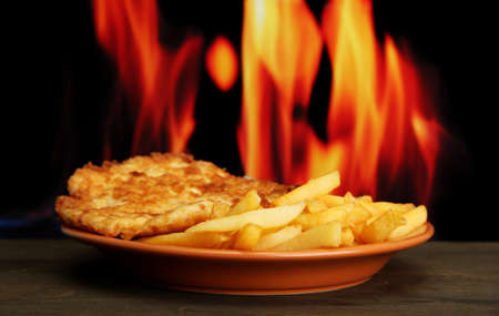 Roast chicken cutlet with french fries,  on fire background photo