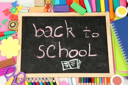 The words Back to School written in chalk on the small school desk with various school supplies close-up photo